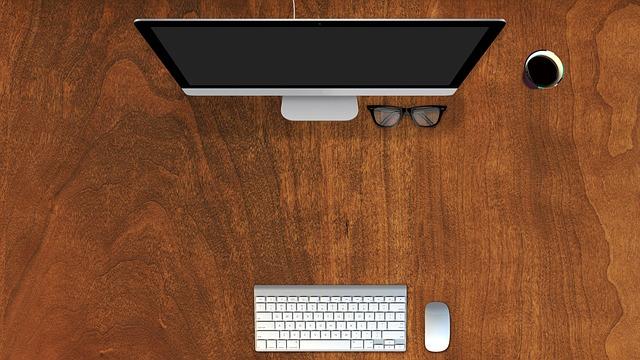 Počítač a klávesnica na bielom stole.jpg