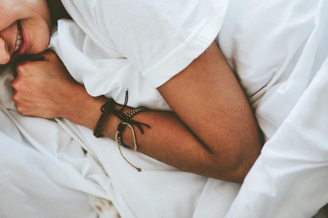 Žena s hnedými náramkami na ruke leží v perinách na posteli a usmieva sa.jpg
